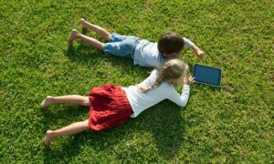 Children lying on grass, using digital tablet together